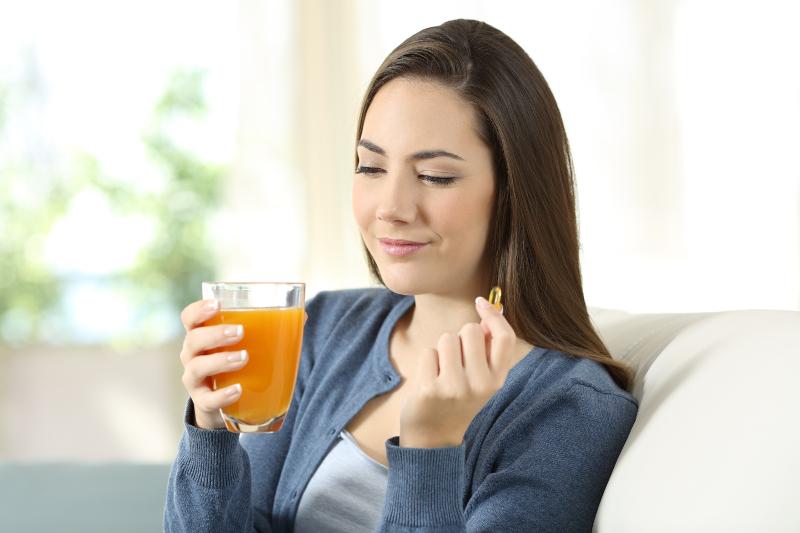 RLS-Patientin nimmt Tablette und trinkt Grapefriutsaft