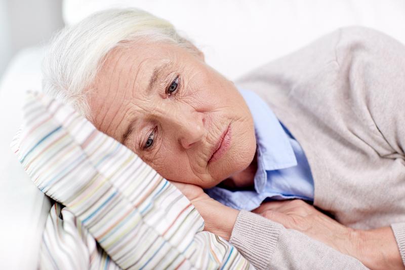 Alte Frau leidet an Restless Legs Syndrom ist deshalb sehr niedergeschlagen. Das RLS verhindert, dass Sie genug schlafen kann.